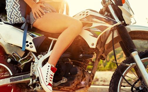 mulher em posição de pilotagem de uma moto